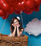 Small cute girl flying on red heart balloons Valentines day Stock Image