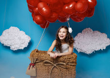 Small cute girl flying on red heart balloons Valentines day Royalty Free Stock Photos
