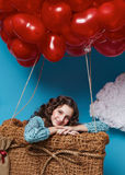 Small cute girl flying on red heart balloons Valentines day Stock Images