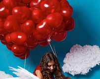 Small cute girl flying on red heart balloons Valentines day Royalty Free Stock Image