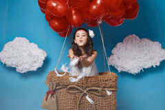 Small cute girl flying on red heart balloons Valentines day Royalty Free Stock Images