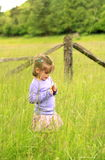 Small Cute Girl in Grassy Field. A little 4yr old girl child picking grass & flowers in a grassy field in the country Stock Photo