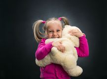 Small cute girl holds toy bear. Little cute girl holds toy bear on grey Royalty Free Stock Photos