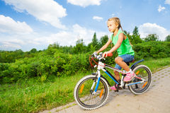 Small cute girl riding children bike on road Stock Images