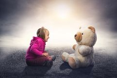Small cute girl sits and looks at toy bear Royalty Free Stock Photo