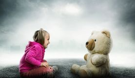 Small cute girl sits and looks at toy bear Stock Images