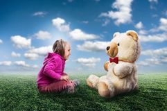 Small cute girl sits and looks at toy bear Royalty Free Stock Photography