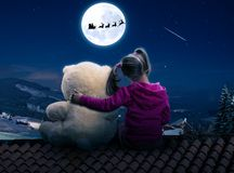 Small cute girl sitting on the roof with toy bear Stock Photo