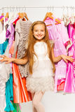 Small cute girl standing between hangers in shop Stock Image