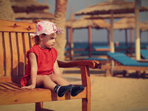 Small cute kid girl sitting on the bench on beach background Stock Photos