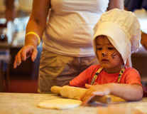 Small chef girl cooking homemade cake, using rolling pin with grandma on kitchen. Small cute kid in a kitchen with a face art cat cooking homemade bread stock image
