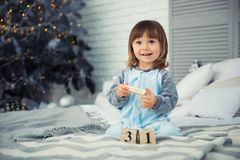 Free Small Cute Little Girl Is 2 Years Old Sitting Near Christmas Tree And Looking At The Calendar. 31th Of December. Stock Image - 105550721