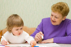 Small cute painting girl with grandma. At home Stock Photos