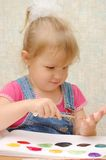 Small cute painting girl at home Stock Photography