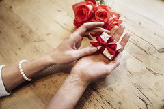 Small cute present box with bow in beautiful woman hands. Focus on bow. Red roses flowers behind on wooden table. St. Valentine`s Stock Image
