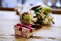 Small cute present box with bow at wooden table, rose flowers behind. St. Valentine`s day concept Stock Photo