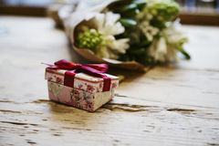 Small cute present box with bow at wooden table, rose flowers behind. St. Valentine`s day concept. Royalty Free Stock Photos