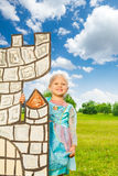 Small cute princess stands behind the drawn tower Stock Photo
