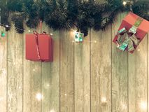 Small cute red festive gift boxes, Christmas, New Year`s decoration on the background of green Christmas-tree branches with. Needles and glowing garlands on royalty free stock photo