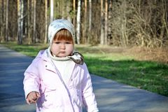 Little cutel girl walking along a path in a spring park. Small cute thoughtful girl walks along path in spring park. Concept springtime walk with child Royalty Free Stock Image