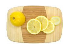 Small cutting board with lemon and slices Royalty Free Stock Photo