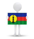 Small 3d man holding a flag of New Caledonia Royalty Free Stock Image