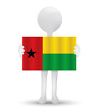 Small 3d man holding a flag of Republic of Guinea-Bissau Royalty Free Stock Photography