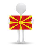Small 3d man holding a flag of Republic of Macedonia Royalty Free Stock Photography
