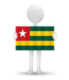 Small 3d man holding a flag of Togolese Republic Royalty Free Stock Photos
