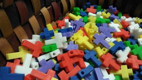 Tiny Plastic Crosses. Small 3d printed plastic colorful crosses in a basket to handout as a giveaway Stock Image