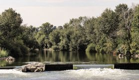 Small dam on the Boise River. A very small dam highlights the Boise River with green trees on the river banks stock image