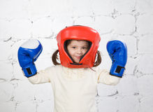 Portrait of the small dark-haired girl in a protective helmet an. Small dark-haired girl in a protective helmet and boxing gloves costs in a fighting rack stock photography