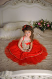 Small dark-haired girl in a red dress Stock Image