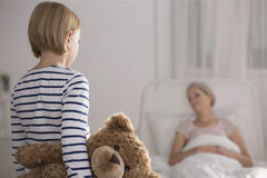 Daughter visiting mother in hospice. Small daughter holding teddy bear visiting sick mother in hospice Royalty Free Stock Photography