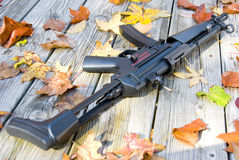 Small but deadly. Picture of a sub machine gun surrounded by leaves Stock Photos
