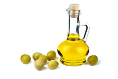 Small decanter with olive oil and some olives near. Isolated on the white background Royalty Free Stock Photos