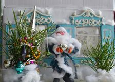 Small decorated New Year tree with Father Frost and old house in the background. Horizontal retro Christmas photo of plasticine Santa, Russian house and New Year Stock Image