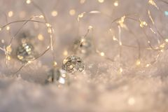 Small decorative balls with a mirror and a luminous garland on a snow. Blurred festive gray background with white bokeh. Small decorative balls with a mirror stock photos