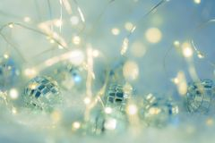 Small decorative balls with a mirror and a luminous garland on a snow. Blurred festive gray background with white bokeh. Small decorative balls with a mirror royalty free stock photo