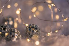 Small decorative balls with a mirror and a luminous garland on a snow. Blurred festive gray background with yellow bokeh. Decorative balls with a mirror and a royalty free stock photography