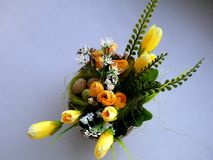 Small decorative basket with yellow colors. And a little birdie and decorative eggs Stock Images