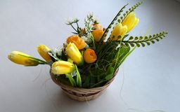 Small decorative basket with yellow colors. And a little birdie and decorative eggs Stock Photography
