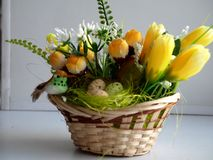 Small decorative basket with yellow colors. And a little birdie and decorative eggs Royalty Free Stock Photography