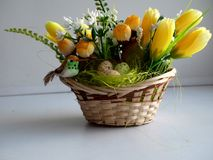 Small decorative basket with yellow colors. And a little birdie and decorative eggs Stock Image