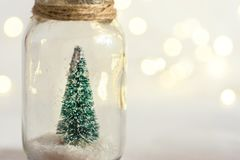 Small decorative Christmas tree in glass jar tied with twine. Snow golden garland bokeh sparkling lights. New Year greeting card. Poster with copy space stock photography