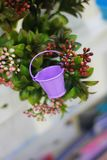 Garden miniature purple bucket on a background of bushes stock image