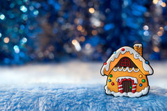 Small decorative house, simulating gingerbread on foreground and. Beautiful Golden-blue bokeh on the background. Christmas and New Year background Stock Images