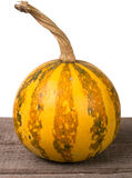 Small decorative orange pumpkin on a wooden board isolated  white background Stock Photography