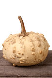 Small decorative pumpkin on a wooden board isolated white background Royalty Free Stock Images