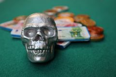 Skull with money on green table royalty free stock photography